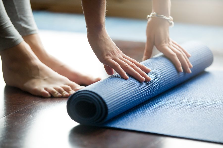Close-up of young woman folding blue yoga or fitness mat after working out at corner canyon recovery