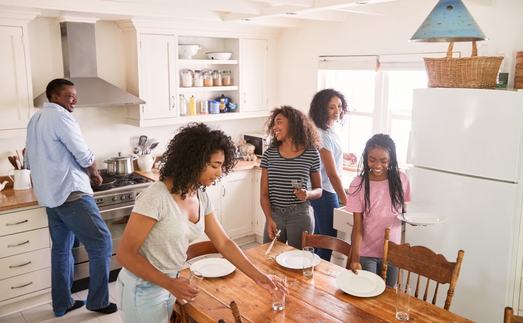 Family With Teenage Daughters Laying Table For Meal In Kitchen