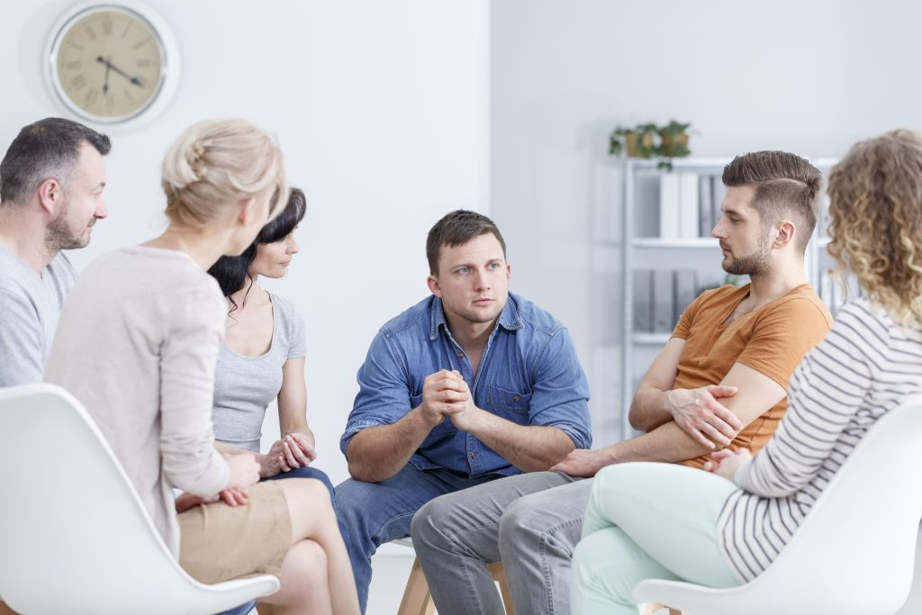 Focused man talking to people in group therapy