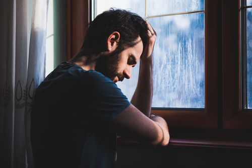 A man depressed by a window.